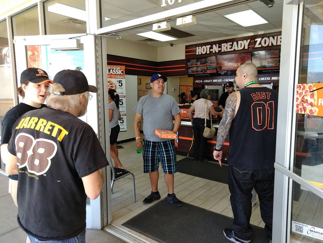 Selwyn Harris/Pahrump Valley times Local resident Brian Silva, center, was one of dozens who enjoyed a free lunch courtesy of Little Caesar's on Monday. Silva actually predicted the winner of the  ...