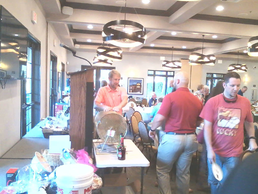 Tom Rysinski/Pahrump Valley Times Attendees drop ping pong balls into the hopper in hopes of winning one of the 160 prizes donated to the Quarter Auction to support youth golf programs in Pahrump.
