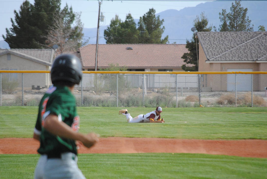Charlotte Uyeno/Pahrump Valley Times Pahrump Valley left fielder Anthony Charles makes a diving catch during a game against Mojave. Charles singled in a run and scored a run during the Trojans' 5- ...