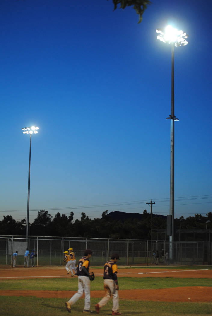 Charlotte Uyeno/Pahrump Valley Times Little League players walk on and off the field between innings under the new lights Tuesday at Ian Deutch Memorial Park.