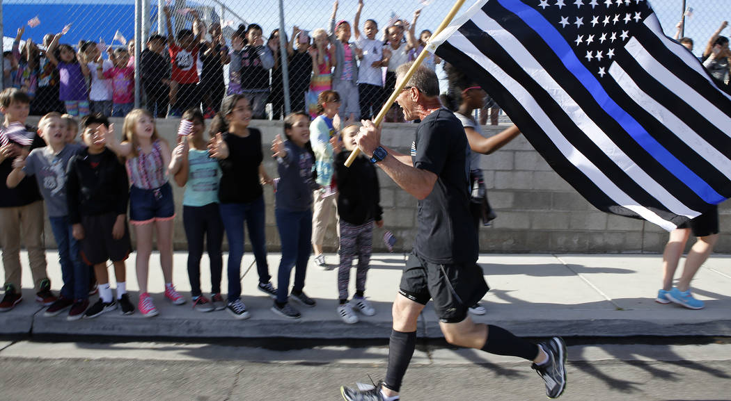 Retired North Las Vegas police chief Joseph Forti, 62, runs pass Marc A. Kahre Elementary School students during the 18th annual Nevada law enforcement officers memorial run on Wednesday, April 26 ...