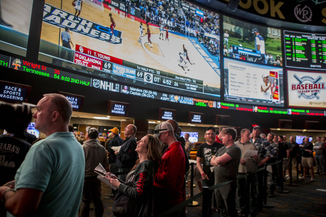 Sports betters line up to place their bets as games play overhead on giant screens at the Westgate Superbook in Las Vegas on Thursday, March 15, 2018. (Patrick Connolly/Las Vegas Review-Journal) @ ...