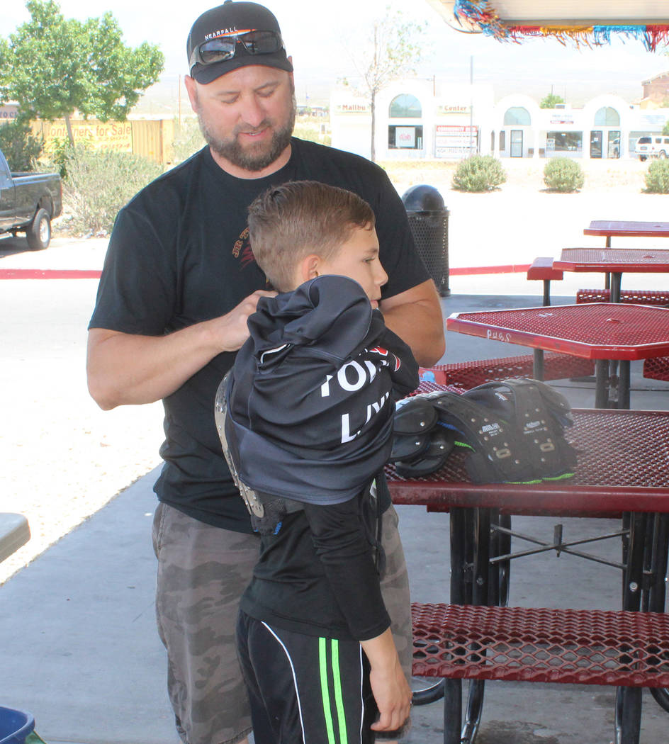 Tom Rysinski/Pahrump Valley Times Johnny O'Neal, president of Pahrump Youth Sports, fits 10-year-old Austin Alvarez with football equipment on Saturday at the Sonic on Route 160 on Pahrump.