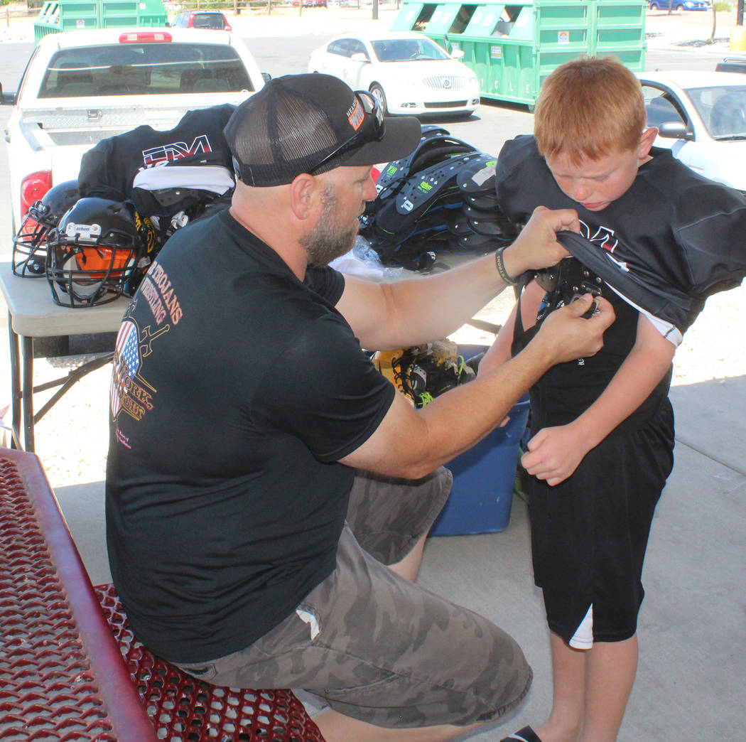 Tom Rysinski/Pahrump Valley Times Chance Brown, 9, gets some help sizing football equipment from Pahrump Youth Sports President Johnny O'Neal on Saturday during football sign-ups at the Sonic on R ...