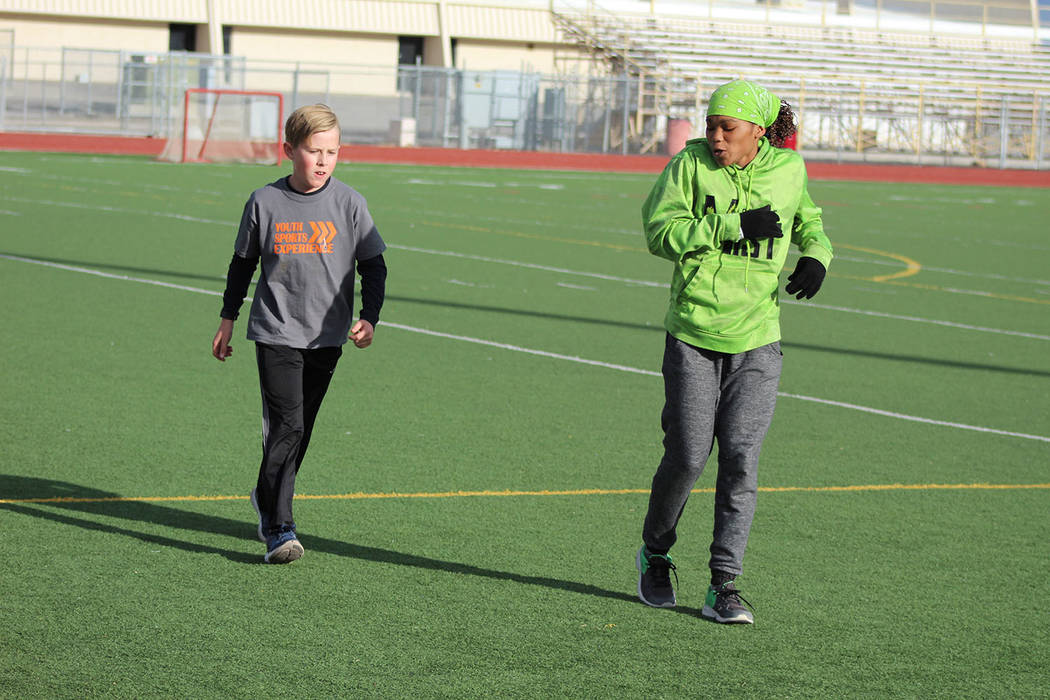"""Tom Rysinski/Pahrump Valley Times Dominique Maloy leads Dane Clayton, 11, in drills during a session of her """"A Youth Sports Experience"""" on March 17 on the football field at Pahrump Valley High School."""