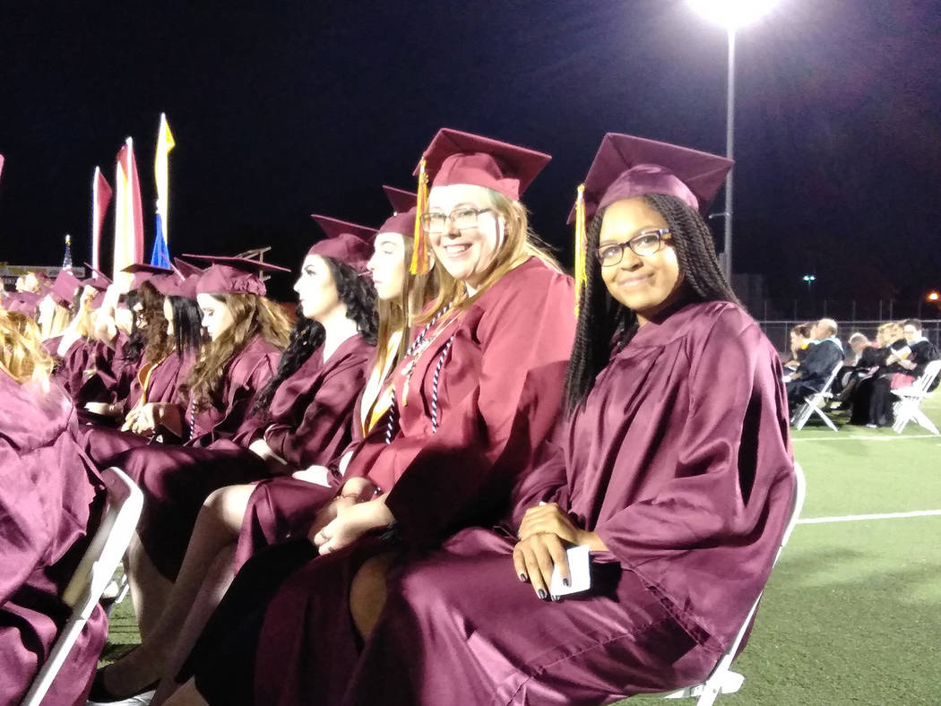 """Selwyn Harris/Pahrump Valley Times PVHS Seniors Irene Tucker, left and Jessica Turner await their respective turn to """"make the walk"""" during the Friday May 25 graduation ceremony on the football field."""