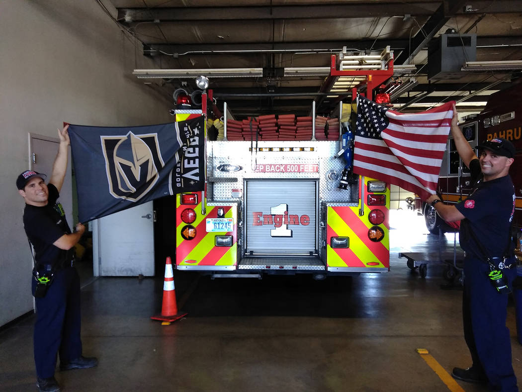 Selwyn Harris/Pahrump Valley Times Pahrump Valley Fire and Rescue Services crew members Matt Garcia, left and Billy Kehoe, right, display the American and Las Vegas Golden Knights flags from the r ...