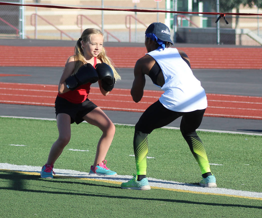 "Tom Rysinski/Pahrump Valley Times Dominique Maloy puts McKenna Cunningham, 10, through a drill during Sunday morning's session of Maloy's ""A Youth Sports Experience"" at Pahrump Valley High School' ..."