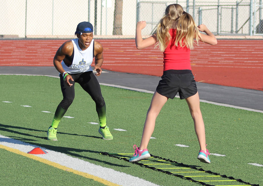 "Tom Rysinski/Pahrump Valley Times Dominique Maloy shouts encouragement to McKenna Cunningham, 10, during ""A Youth Sports Experience"" session Sunday on the football field at Pahrump Valley High School."