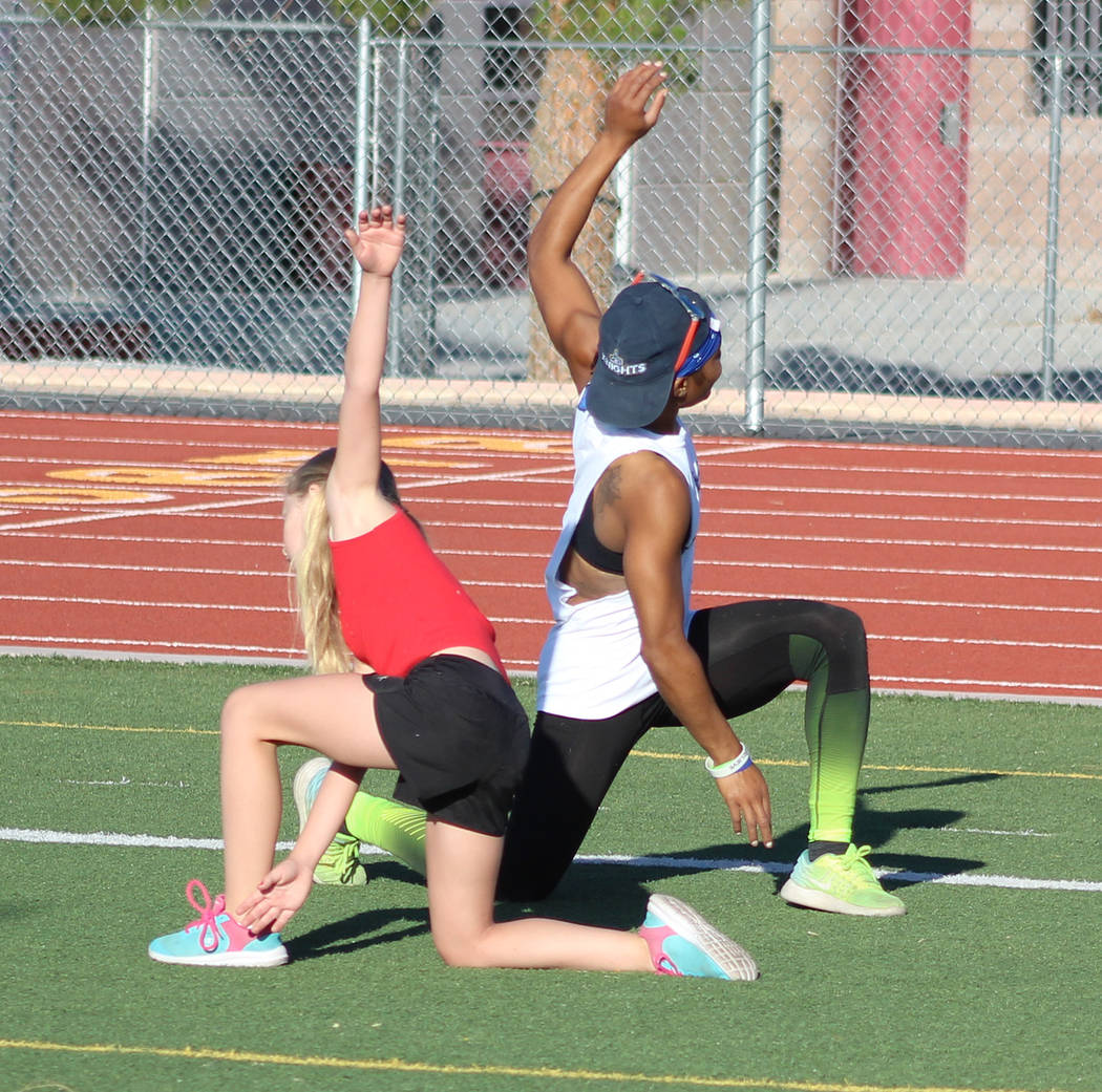 Tom Rysinski/Pahrump Valley Times McKenna Cunningham, 10, and Dominique Maloy stretch before drills on Sunday morning at Pahrump Valley High School.