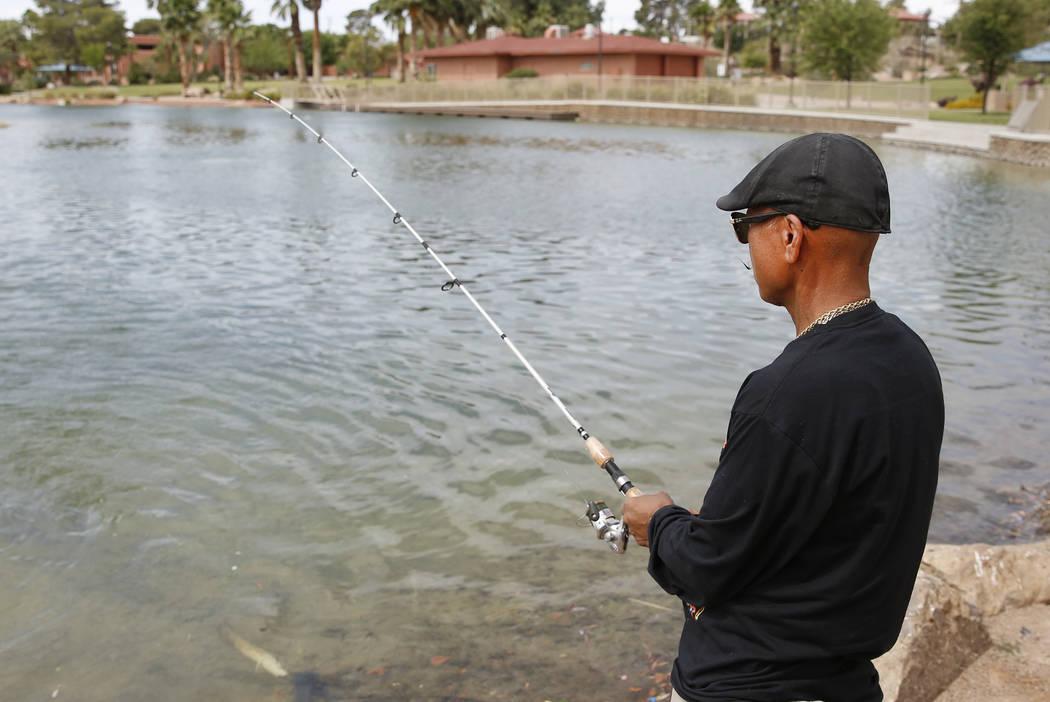 Bizuayehu Tesfaye/Las Vegas Review-Journal Renaldo Cabebe fishes at Lorenzi Park on Thursday, June 8, 2017, in Las Vegas. The Nevada Department of Wildlife will celebrate free fishing day Saturday.