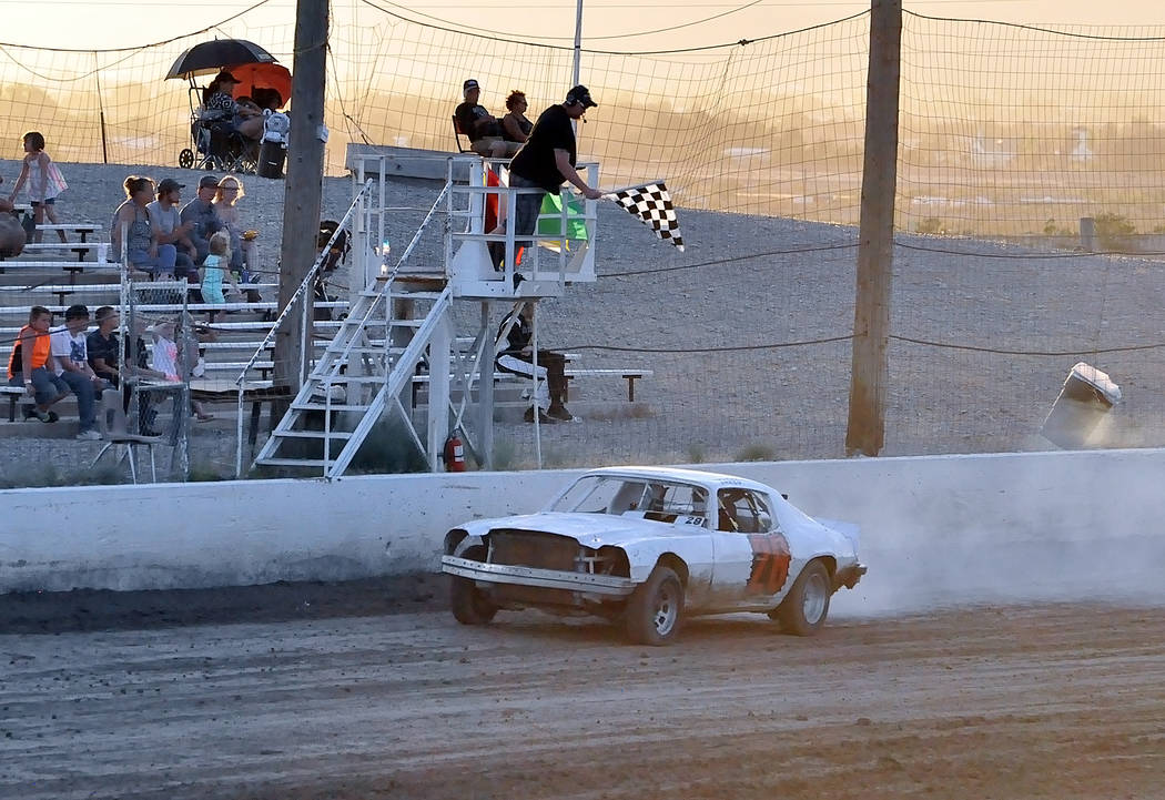 Horace Langford Jr./Pahrump Valley Times Jared Ward takes the checkered flag from flagman Dale Geissler in the Hobby Stocks event on Saturday night at Pahrump Valley Speedway.