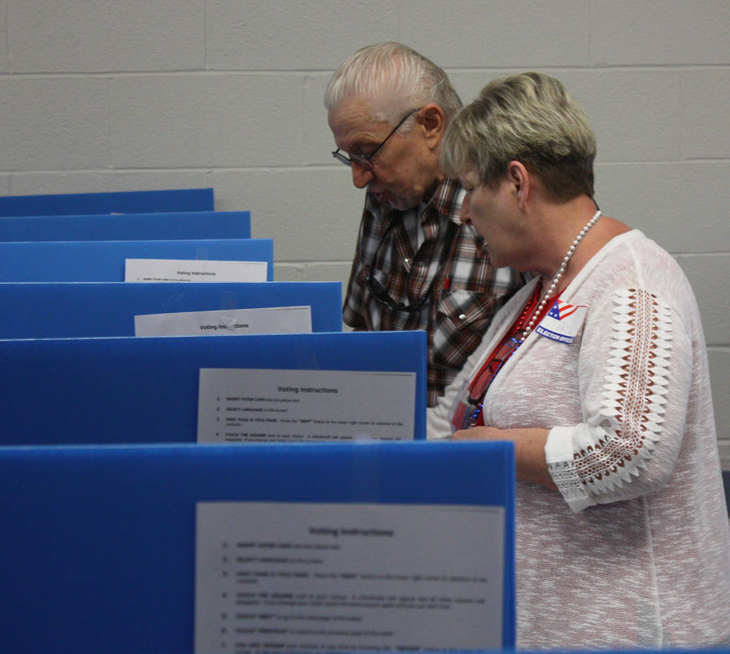Robin Hebrock/Pahrump Valley Times An election site workers is pictured assisting a local gentleman in getting to know the new Nye County voting machines, used for the first time this primary elec ...
