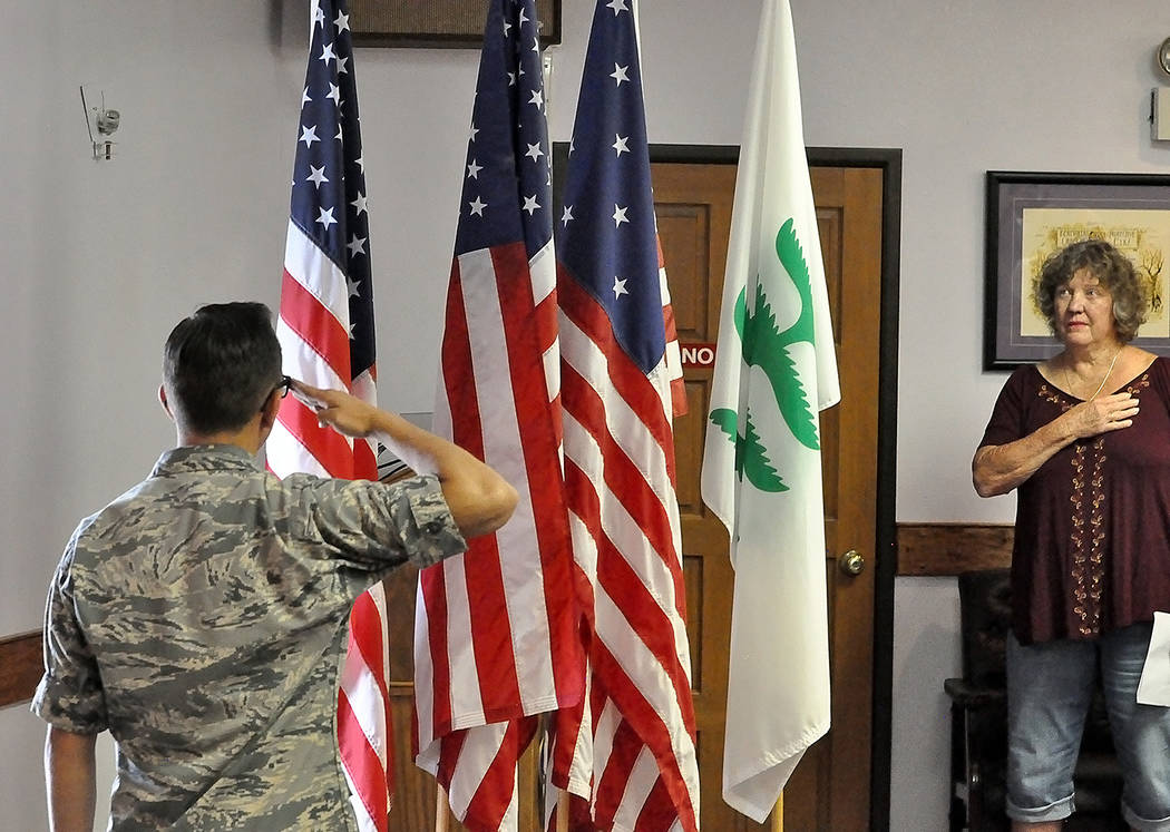 Horace Langford Jr./Pahrump Valley Times A member of Pahrump's Civil Air Patrol salutes the flag as a Pahrump Elks Lodge member shows reverence by holding her hand over her heart during Friday's F ...