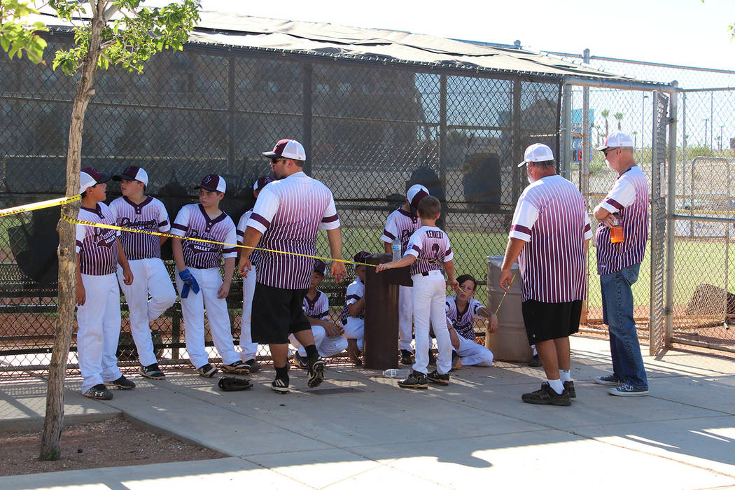 Caroline Thacker/Special to the Pahrump Valley Times P-Town manager John Walker and coaches Richard Swingle and Pete Christiansen talk to their 9-to-11-year-old all-stars before the start of a Dis ...