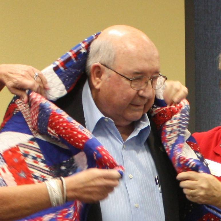 Robin Hebrock/Pahrump Valley Times Veteran William Rettig, U.S. Air Force retired, is pictured in the moment when Nye County Valor Quilters draped his new quilt of valor over his shoulders, envelo ...