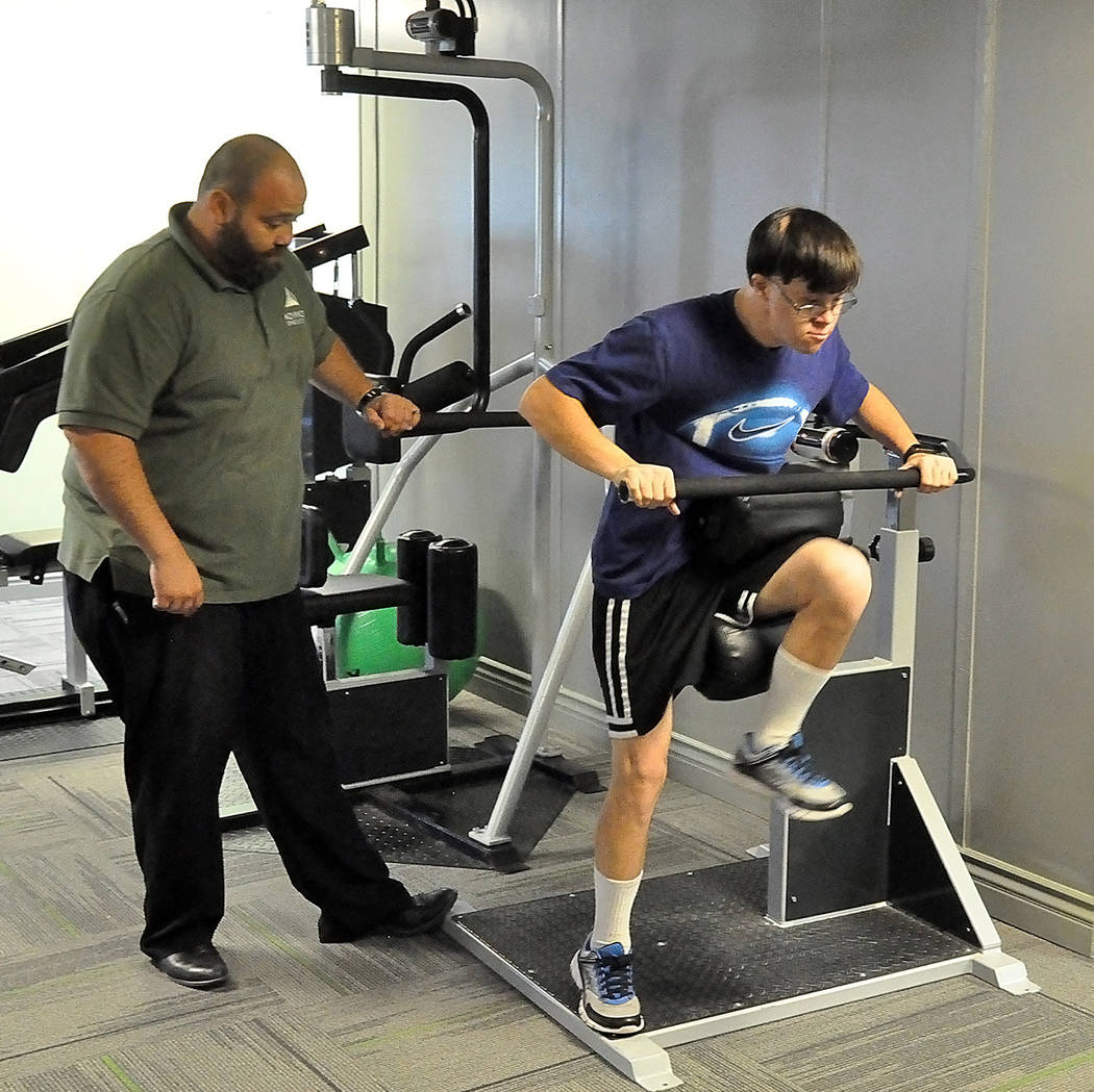 Horace Langford Jr./Pahrump Valley Times Special Olympics athlete Billy Klem works out with Chandy Christensen on Tuesday at Advanced Spine and Posture in Pahrump.