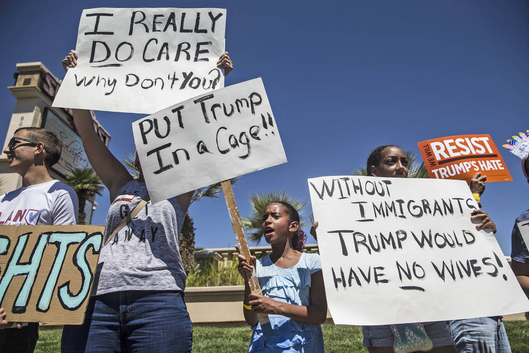 """Paige Faggins, middle, protests outside Suncoast hotel-casino ahead of President Donald Trump's appearance on Saturday, June 23, 2018, in Las Vegas. """"I'm here because Trump is separating fami ..."""