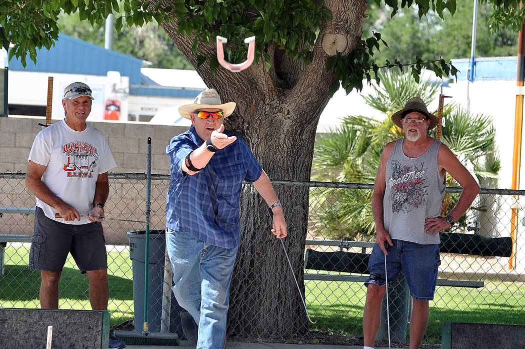 Horace Langford Jr./Pahrump Valley Times Dennis Andersen pitches a shoe while Mike Nicosia, left, and Don Brown look on Wednesday morning in Petrack Park's horseshoe pits.