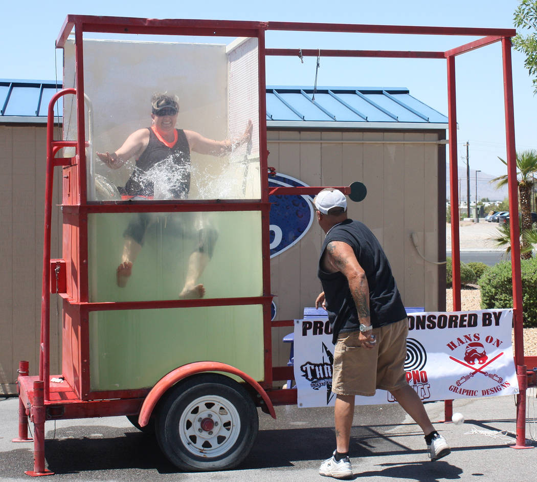 Robin Hebrock/Pahrump Valley Times Nye County Animal Control Officer Susan Ryhal is pictured falling into the water following an accurate throw at the dunk tank, which was part of the Car Studio f ...