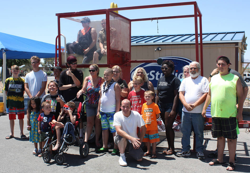 Robin Hebrock/Pahrump Valley Times Gathering together to pose for a photo, the many members and volunteers of PDOP were obviously enjoying their afternoon during the car wash fundraiser held to su ...