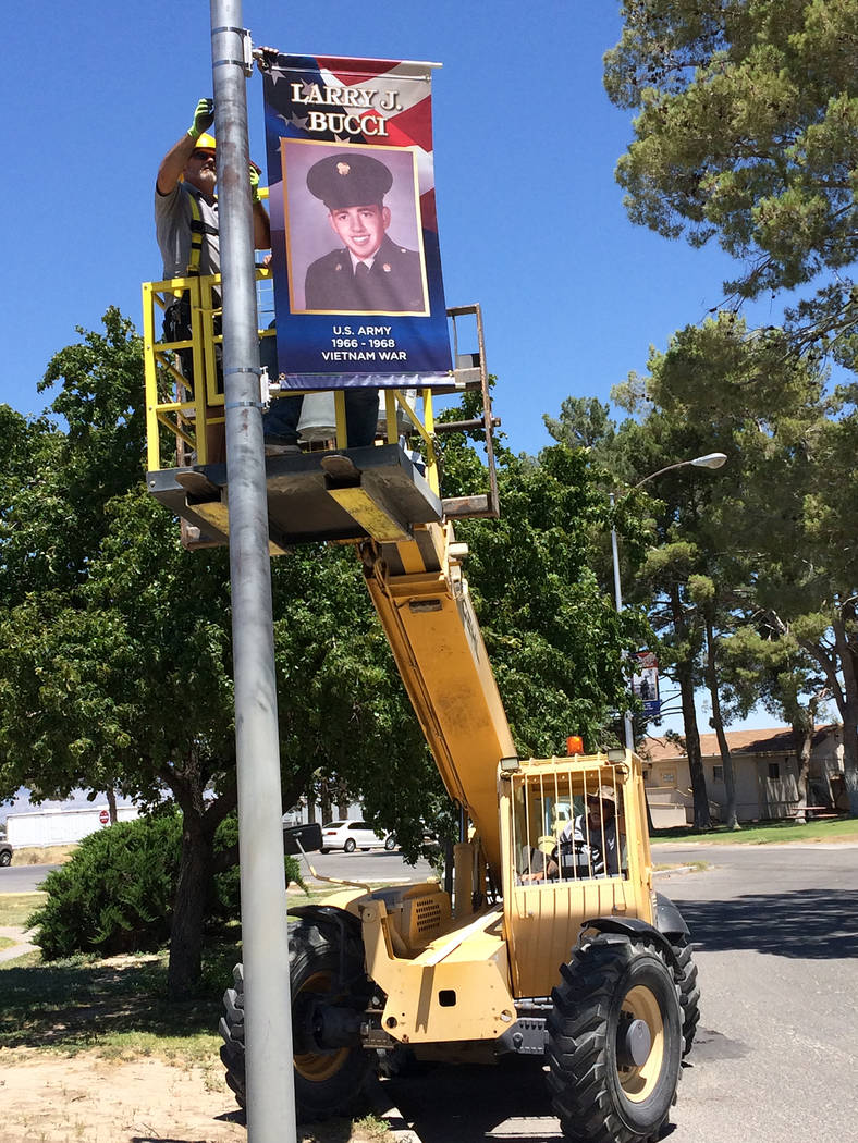 Robin Hebrock/Pahrump Valley Times Nye County Buildings and Grounds crews are pictured hanging one of the last pieces in the Veterans Banner Program on Tuesday, July 3.