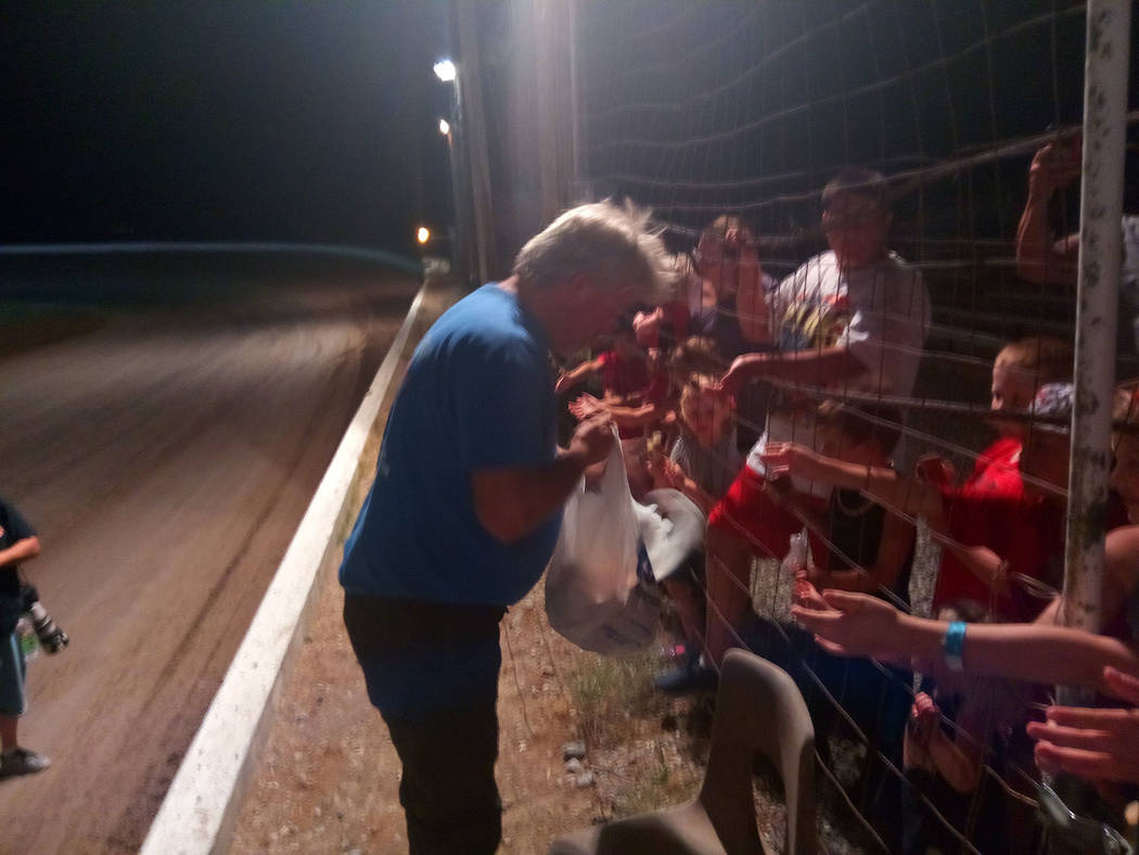 Dale Geissler/Pahrump Valley Times Gary Wyatt hands out wooden cars to kids July 7 at Pahrump Valley Speedway. One of the cars has the race date written on it, and the kid who gets that car can ta ...