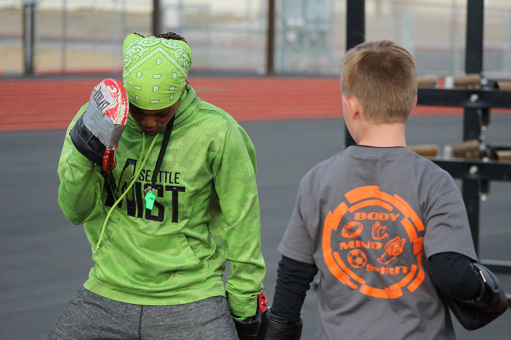 "Tom Rysinski/Pahrump Valley Times Dominique Maloy, left, prepares Dane Clayton, 11, for a drill during her ""A Youth Sports Experience"" on in March at Pahrump Valley High School."