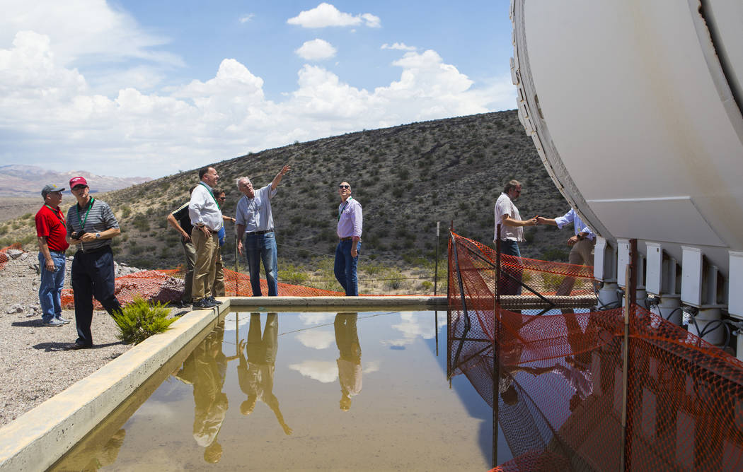 Wiilliam Boyle of the Department of Energy's Office of Nuclear Energy, fourth from left, points to the Yucca Mucker during a congressional tour of Yucca Mountain near Mercury on Saturday, July 14, ...