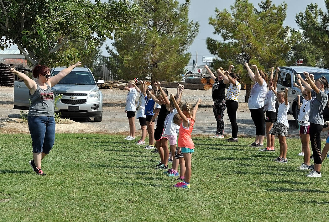 Horace Langford Jr./Pahrump Valley Times Coach Mary Wilson leads a preseason workout of the Pahrump Valley Junior Trojans cheerleaders Saturday at Petrack Park.
