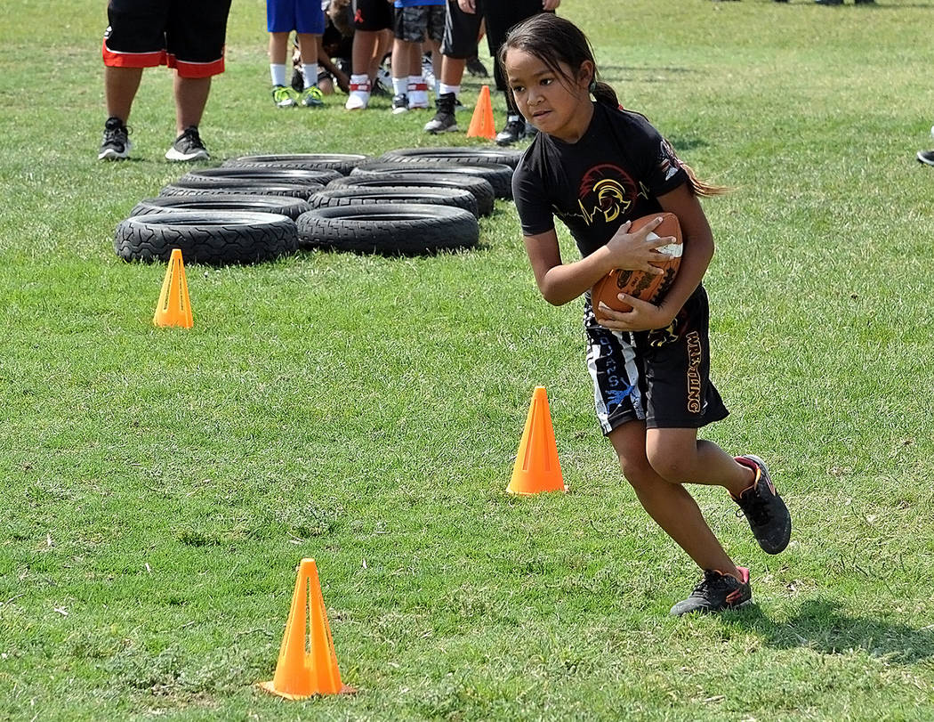 Horace Langford Jr./Pahrump Valley Times Carrying a football through tires and around cones was one of the drills at Pahrump Youth Football's combine July 28 at Petrack Park.