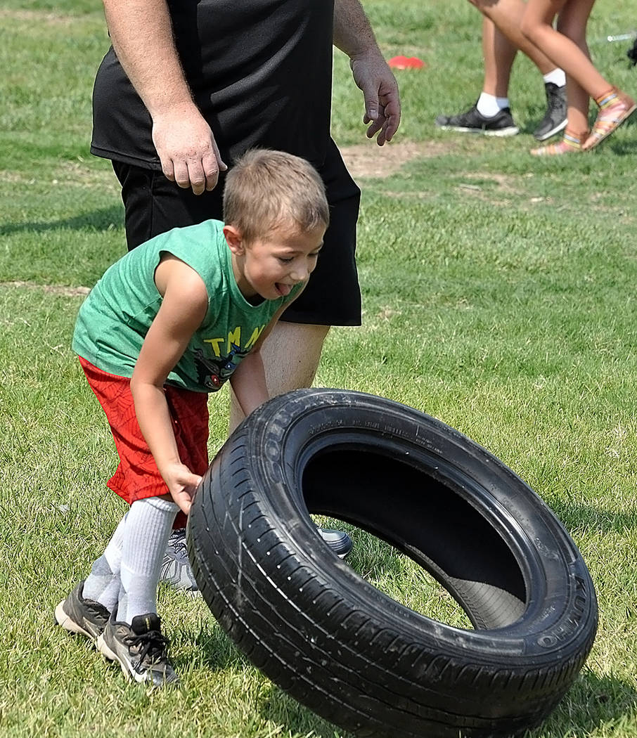 Horace Langford Jr./Pahrump Valley Times Young football players flip over tires, with different sizes for different kids, in a test of strength at Petrack Park during the Pahrump Youth Football co ...