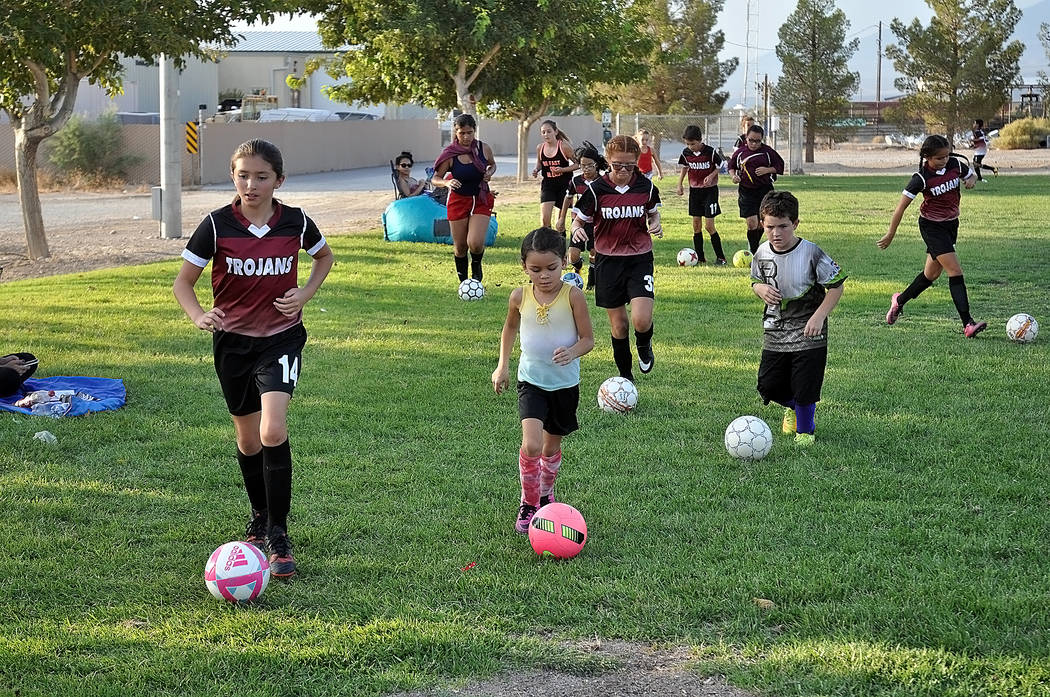 Horace Langford Jr./Pahrump Valley Times Members of the Junior Trojans Soccer Club keep their eyes, and feet, on the balls as they practice dribbling around the field at Petrack Park in Pahrump.