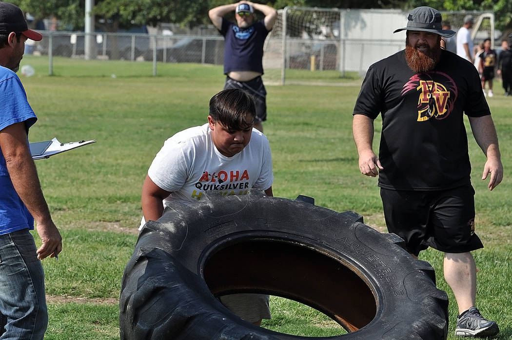 Horace Langford Jr./Pahrump Valley Times Pahrump Valley Junior Trojans coaches tested the strength of their players by having them flip over a tire as many times as they could in 60 seconds during ...