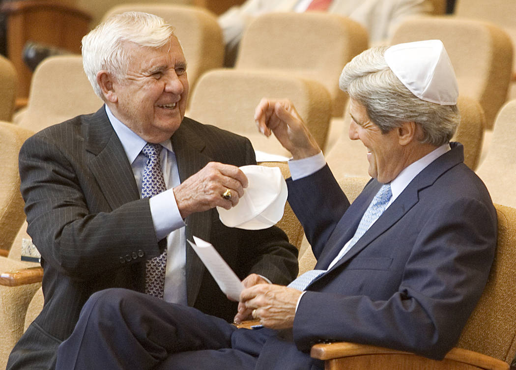 Former Sen. Paul Laxalt, R-Nev., left, asks Sen. John Kerry, D-Mass., for help with his yarmulke before the start of the memorial service for the former Sen. Chic Hecht, R-Nev., at the Temple Beth ...
