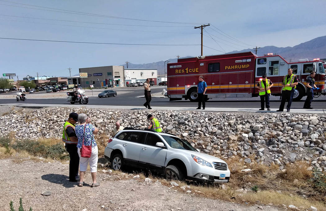 Selwyn Harris/Pahrump Valley Times Pahrump Valley Fire and Rescue Services crews assess the condition of a passenger involved in a two-vehicle crash along southbound Highway 160 in front of Wells ...