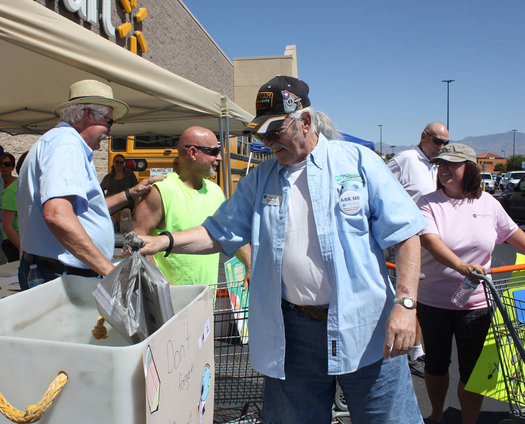 Robin Hebrock/Pahrump Valley Times VEA Ambassador Phil Raneri is seen placing a bag full of school supplies into a bucket. Utility officials were thrilled to announce that 49 total buckets had bee ...