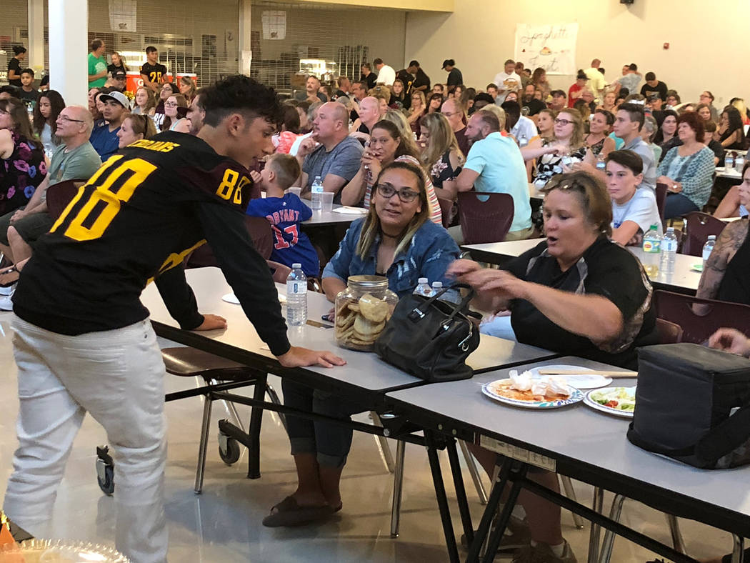 Tom Rysinski/Pahrump Valley Times Tony Margiotta delivers a jar of cookies to the winning bidder Saturday night at Pahrump Valley High School.