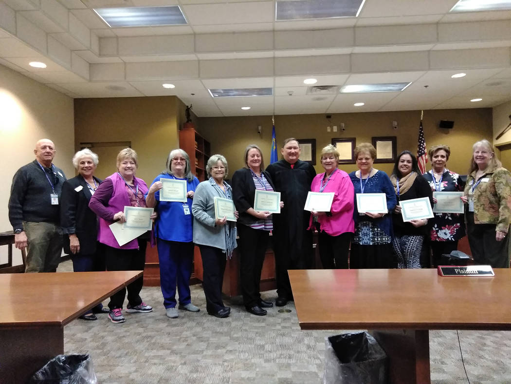 Selwyn Harris/Pahrump Valley Times Fifth Judicial District Court Department-2 Judge, the Honorable Robert W. Lane, center, is flanked by newly sworn CASA volunteers on Nov. 6, 2017. CASA trains v ...