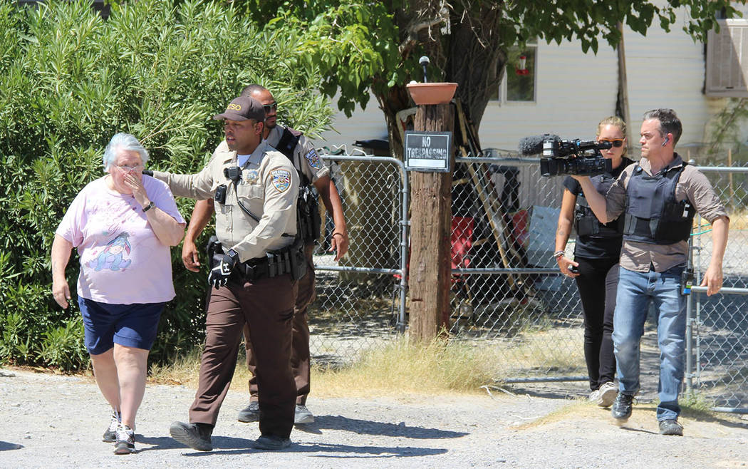 Charles Hoover/Special to the Pahrump Valley Times Nye County Sheriff's Deputies escort a resident to safety from the fire grounds. Fire Chief Scott Lewis said though the exact cause of the fire i ...