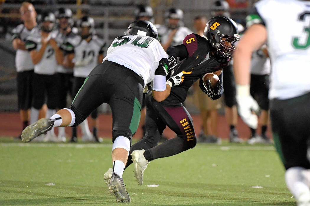 Peter Davis/Special to the Pahrump Valley Times Casey Flennory of Pahrump Valley tries to elude Virgin Valley defensive end Riley Waite during the Bulldogs' 26-24 win over the Trojans last Friday ...
