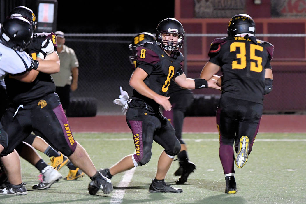Peter Davis/Special to the Pahrump Valley Times Pahrump Valley quarterback Tyler Floyd keeps an eye on the line while handing off to Nico Velazquez during last week's game against Virgin Valley in ...