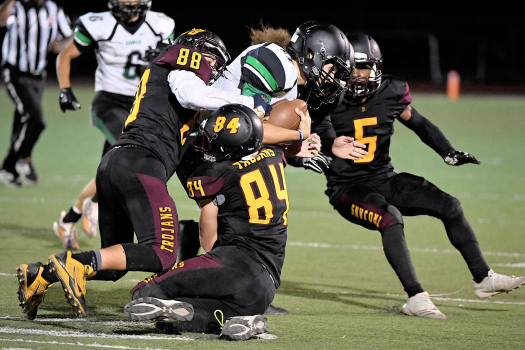 Peter Davis/Special to the Pahrump Valley Times Antonio Margiotta (88) and Andrew Avena (84) of Pahrump Valley combine to bring down Virgin Valley receiver David-Shane Carson as Casey Flennory mov ...