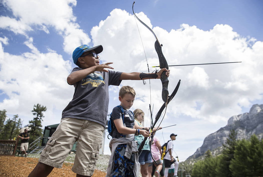 Benjamin Hager/Las Vegas Review-Journal James Mendoza, left, practices his archery skills during Youth Adventure Day on July 20 at Lee Canyon.