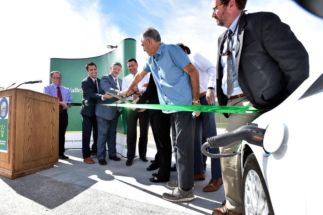 David Becker/Las Vegas Review-Journal Nevada Gov. Brian Sandoval, center, with other dignitaries cut a ribbon to dedicate the first electric car charging station along U.S. Highway 95 Tuesday, Ma ...