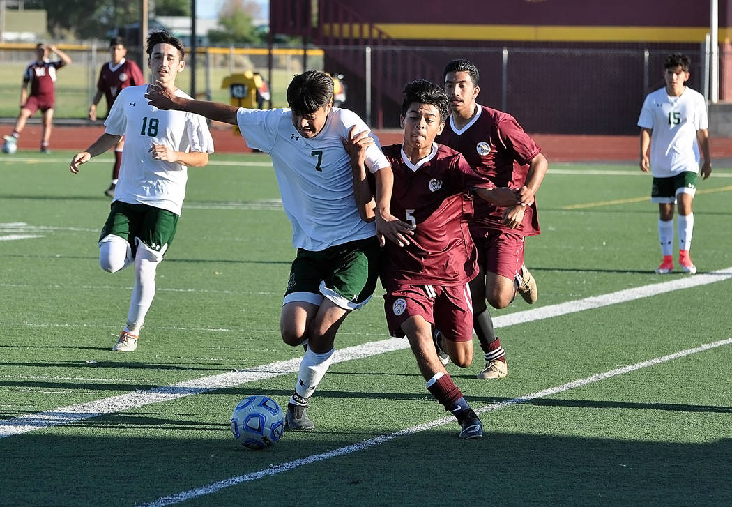 Horace Langford Jr./Pahrump Valley Times Freshman Christopher Vega battles a Mojave defender for the ball during Thursday's game in Pahrump. Vega scored the winning goal in the Trojans' 2-1 victory.