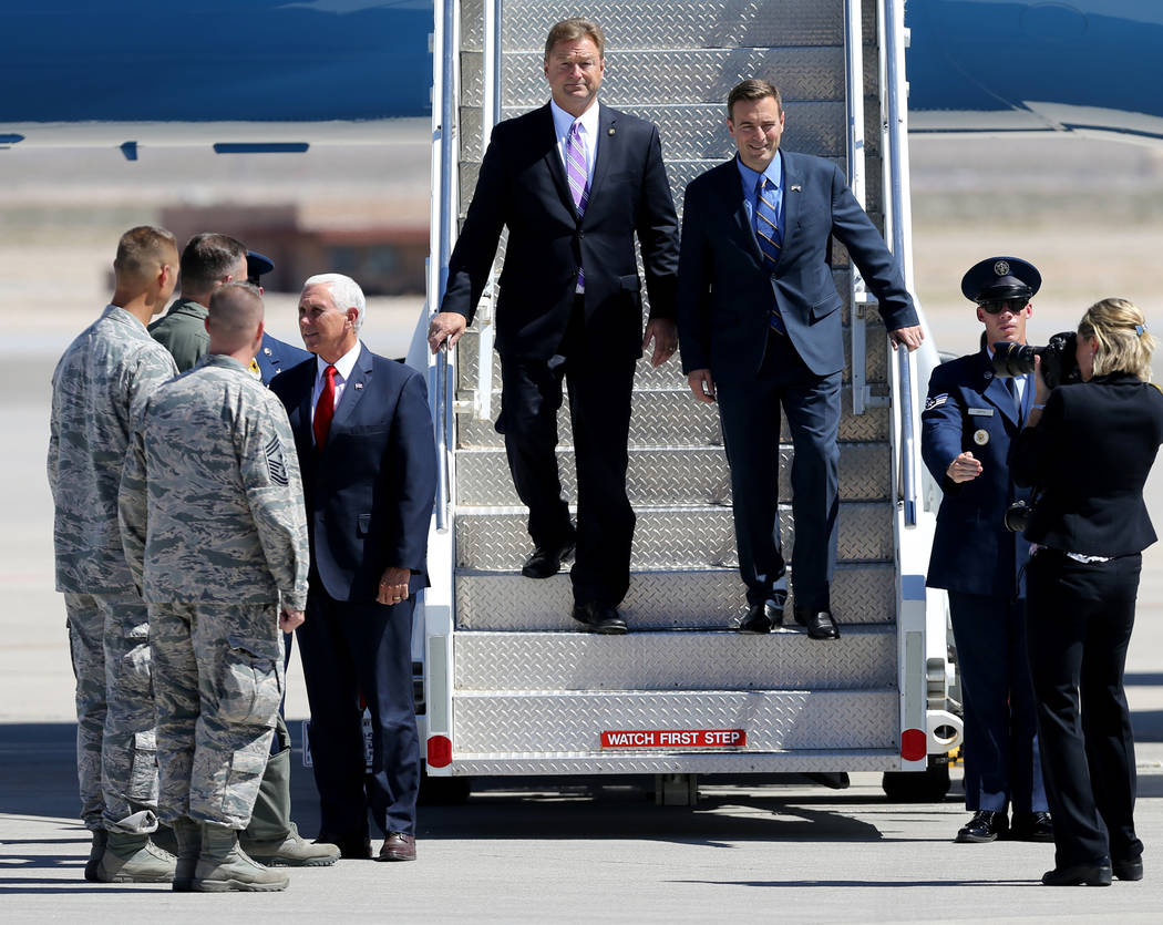 Vice President Mike Pence meets with Brig. Gen. Rob Novotny as U.S. Sen. Dean Heller, top left, and Attorney General Adam Laxalt exit Air Force Two after landing at Nellis Air Force Base in Las Ve ...