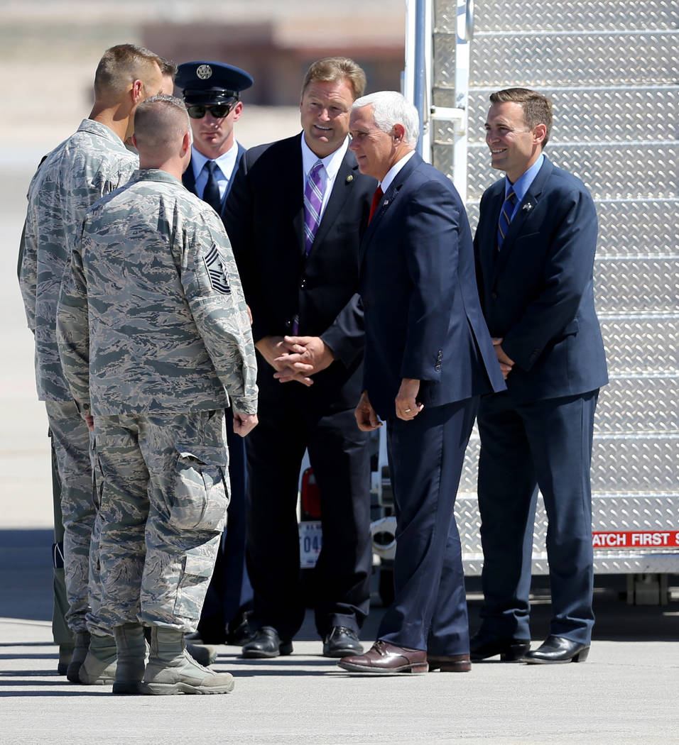Vice President Mike Pence, second from right, Attorney General Adam Laxalt, right, and U.S. Sen. Dean Heller meet with officials after exiting Air Force Two at Nellis Air Force Base in Las Vegas F ...