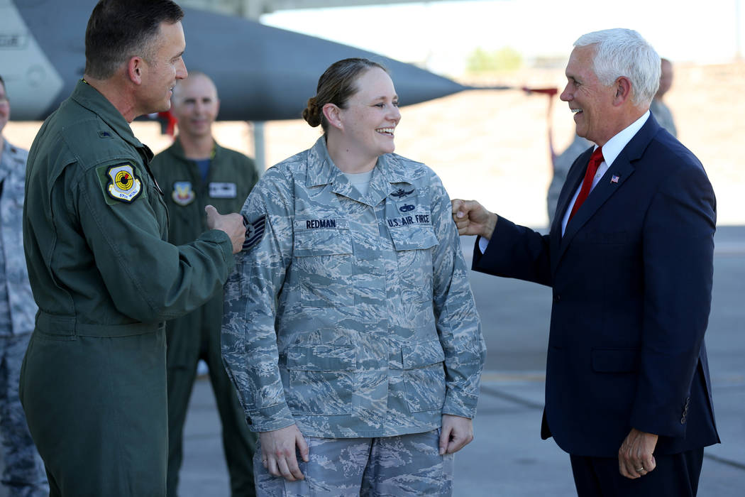 Vice President Mike Pence, right, and Brig. Gen. Rob Novotny, tack Staff Sgt. Vanessa Redman after promoting her to technical sergeant at Nellis Air Force Base in Las Vegas Friday, Sept. 7, 2018. ...