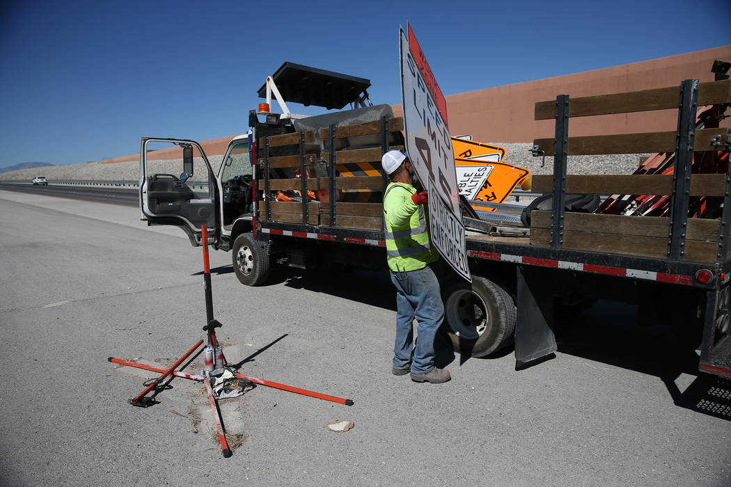 Cesar Escobar, traffic control supervisor for Las Vegas Paving Corporation, removes a work zone sign on the 215 Beltway near Lone Mountain Road in Las Vegas, Friday, Aug. 31, 2018. Clark County in ...